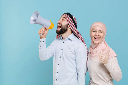 Funny couple friends arabian muslim man wonam in keffiyeh kafiya ring igal agal hijab clothes isolated on blue background.
