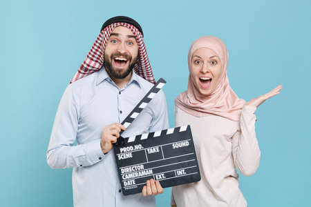 Shocked couple friends arabian muslim man wonam in keffiyeh kafiya ring igal agal hijab clothes isolated on blue wall background.
