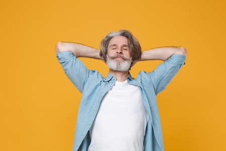 Elderly gray-haired mustache bearded man in casual blue shirt posing isolated on yellow wall background studio portrait. Imagens
