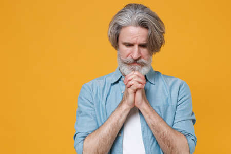 Elderly gray-haired mustache bearded man in casual blue shirt posing isolated on yellow wall background studio portrait. Stock fotó