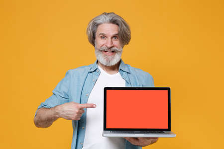 Funny elderly gray-haired mustache bearded man in casual blue shirt posing isolated on yellow background.