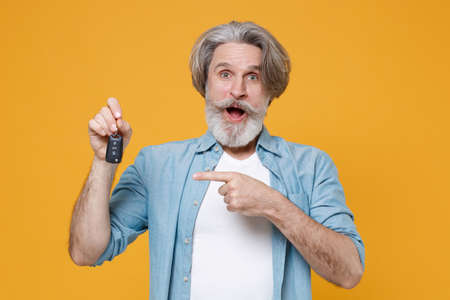 Shocked elderly gray-haired mustache bearded man in casual blue shirt posing isolated on yellow wall background studio.