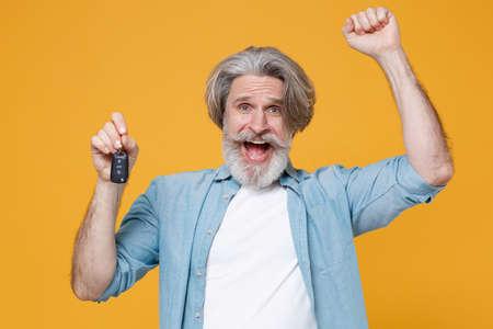 Joyful elderly gray-haired mustache bearded man in casual blue shirt posing isolated on yellow wall background studio.