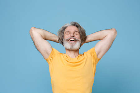 Relaxed elderly gray-haired mustache bearded man in casual yellow t-shirt isolated on blue background studio portrait.