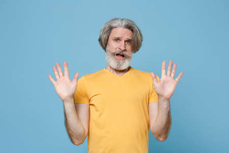 Shocked elderly gray-haired mustache bearded man in casual yellow t-shirt posing isolated on blue wall background studio. Stock Photo