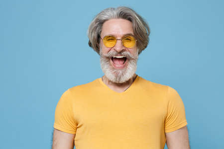Cheerful funny elderly gray-haired mustache bearded man in casual yellow t-shirt, eyeglasses posing isolated on blue background studio portrait.