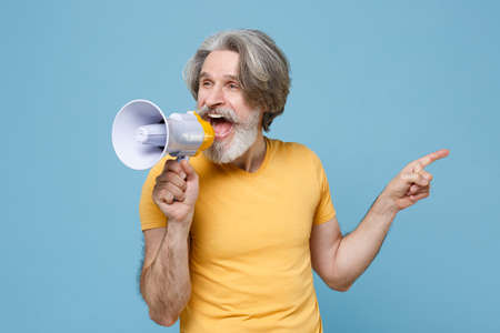 Funny elderly gray-haired mustache bearded man in casual yellow t-shirt posing isolated on blue background. People lifestyle concept. Mock up copy space. Scream in megaphone point index finger aside.