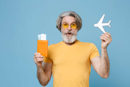 Shocked elderly gray-haired mustache bearded man in casual yellow t-shirt isolated on blue wall background. 免版税图像