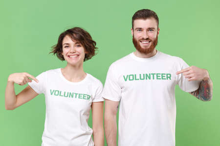 Smiling two young friends couple in white volunteer t-shirt isolated on pastel green background. Voluntary free work assistance help charity grace teamwork concept. Point index fingers on themselves.