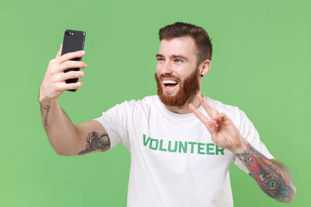 Laughing man in white volunteer t-shirt isolated on pastel green background. Voluntary free work assistance help charity grace teamwork concept. Doing selfie shot on mobile phone showing victory sign.