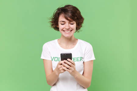 Smiling young brunette woman in white volunteer t-shirt isolated on pastel green background. Voluntary free work assistance help charity grace teamwork concept. Using mobile phone, typing sms message.