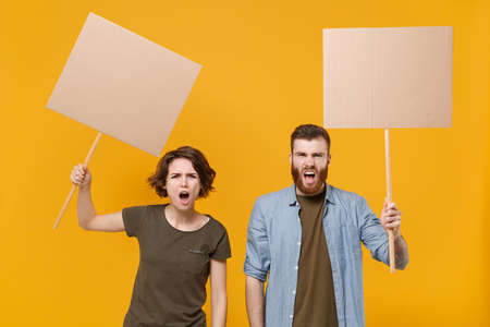 Nervous protesting young two people guy girl hold protest signs broadsheet blank placard on stick, swearing isolated on yellow background studio. Protests strikes pickets concept. Youth against city