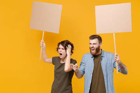Irritated protesting young two people guy girl hold protest signs broadsheet blank placard on stick swearing isolated on yellow background studio. Protests strikes pickets concept. Youth against city
