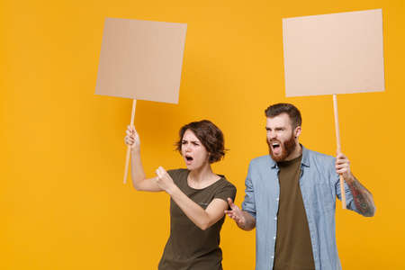 Perplexed protesting young two people guy girl hold protest signs broadsheet blank placard on stick swearing isolated on yellow background studio. Protests strikes pickets concept. Youth against city