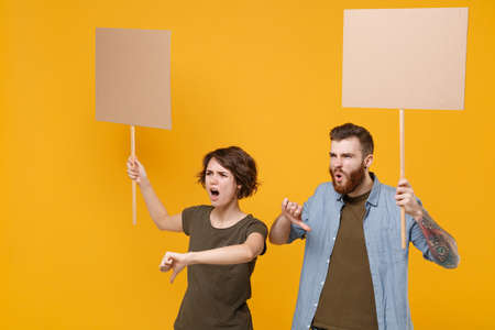 Displeased protesting two people guy girl hold protest signs broadsheet blank placard on stick showing thumbs down isolated on yellow background. Protests strikes pickets concept. Youth against city