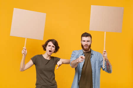 Dissatisfied protesting two people guy girl hold protest signs broadsheet blank placard on stick showing thumb down isolated on yellow background. Protests strikes pickets concept. Youth against city