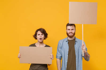 Puzzled protesting young two people guy girl hold protest signs broadsheet blank placard on stick isolated on yellow background studio portrait. Protests strikes pickets concept. Youth against city