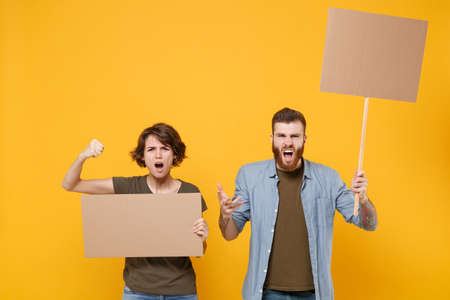 Angry protesting people guy girl hold protest signs broadsheet blank placard on stick isolated on yellow background. Protests strikes pickets concept. Youth against city. Clenching fists, screaming