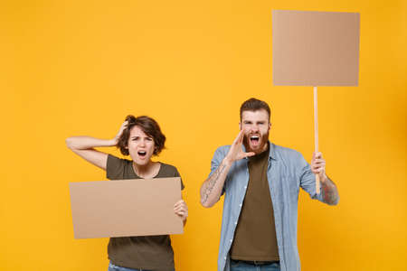 Displeased protesting young people hold protest signs broadsheet blank placard on stick scream with hands gesture isolated on yellow background. Protests strikes pickets concept. Youth against city Archivio Fotografico