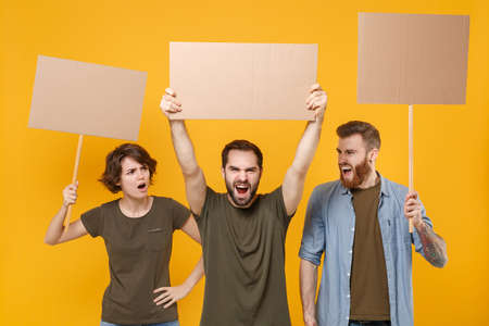 Angry protesting young three people guys girl hold protest signs broadsheet blank placard on stick scream isolated on yellow background in studio. Protests strikes pickets concept. Youth against city.