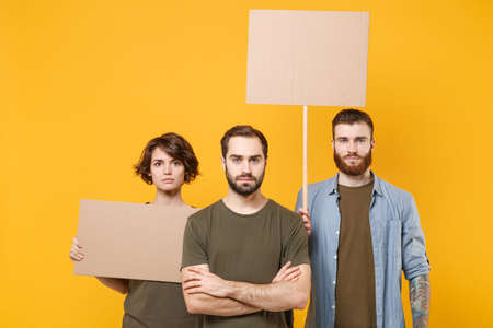 Serious protesting young three people guys girl holding protest signs broadsheet blank placard on stick isolated on yellow background in studio. Protests strikes pickets concept. Youth against city.