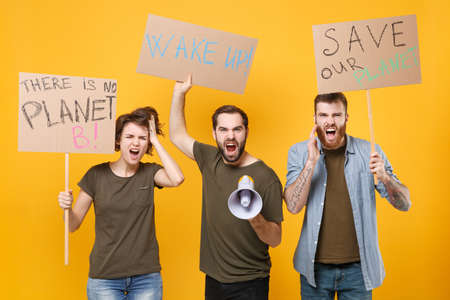 Shocked protesting young three people hold protest signs broadsheet placard scream in megaphone isolated on yellow background. Stop nature garbage ecology environment protection concept. Save planet.