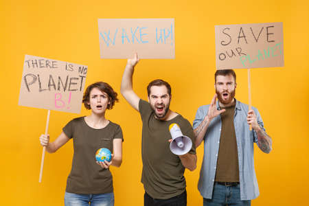 Angry protesting people hold protest signs broadsheet placard world globe scream in megaphone isolated on yellow background. Stop nature garbage ecology environment protection concept. Save planet.