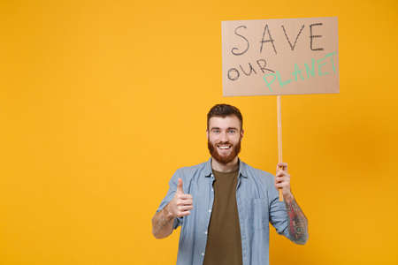 Smiling young protesting man guy hold protest sign broadsheet placard on stick showing thumb up isolated on yellow background. Stop nature garbage ecology environment protection concept. Save planet.
