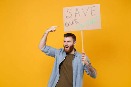 Displeased young protesting man point index finger on protest sign broadsheet placard on stick isolated on yellow background. Stop nature garbage ecology environment protection concept. Save planet. Archivio Fotografico