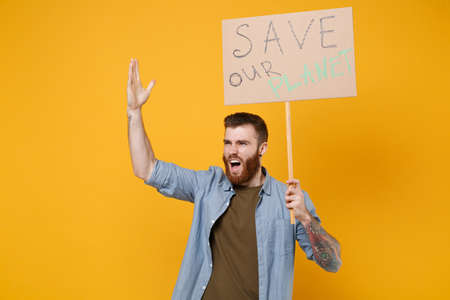 Irritated young protesting man hold protest sign broadsheet placard on stick rising hand scream isolated on yellow background. Stop nature garbage ecology environment protection concept. Save planet.