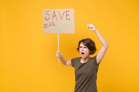 Angry protesting woman hold protest sign broadsheet placard on stick clenching fist screaming isolated on yellow background. Stop nature garbage ecology environment protection concept. Save planet.