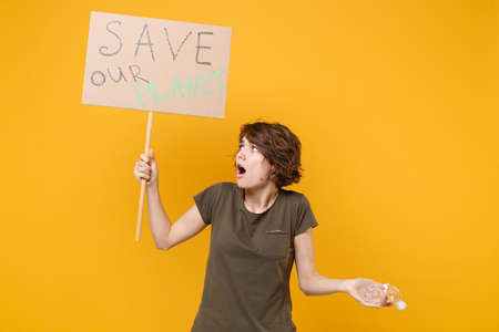 Preoccupied young protesting woman hold protest sign broadsheet placard on stick plastic bottle isolated on yellow background. Stop nature garbage ecology environment protection concept. Save planet.