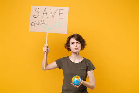 Displeased young protesting girl hold protest sign broadsheet placard on stick Earth world globe isolated on yellow background. Stop nature garbage ecology environment protection concept. Save planet.