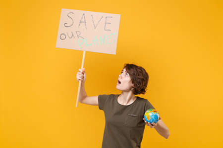 Puzzled young protesting woman hold protest sign broadsheet placard on stick Earth world globe isolated on yellow background. Stop nature garbage ecology environment protection concept. Save planet.
