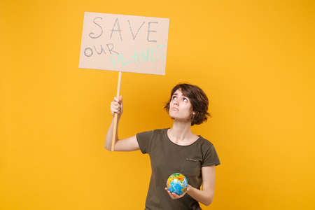 Upset young protesting woman hold protest sign broadsheet placard on stick Earth world globe isolated on yellow background. Stop nature garbage ecology environment protection concept. Save planet.