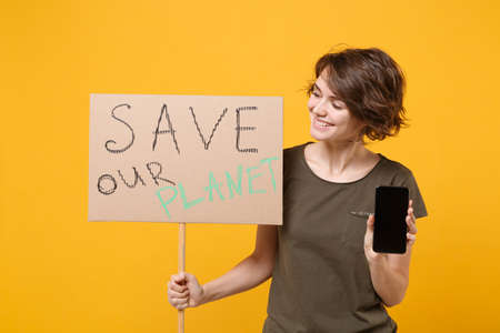 Pretty protesting woman hold protest broadsheet placard mobile phone with blank empty screen isolated on yellow background. Stop nature garbage ecology environment protection concept. Save planet.