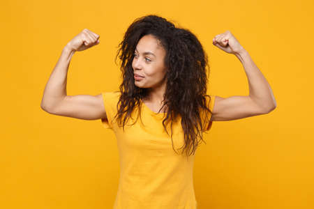 Smiling young african american woman girl in casual t-shirt posing isolated on yellow orange background studio portrait. People emotions lifestyle concept. Mock up copy space. Showing biceps, muscles.