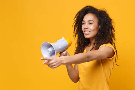 Smiling young african american woman girl in casual t-shirt posing isolated on yellow orange wall background. People lifestyle concept. Mock up copy space. Hold megaphone, pointing index finger aside.