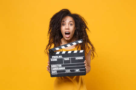 Shocked young african american woman girl in casual t-shirt posing isolated on yellow orange wall background. People lifestyle concept. Mock up copy space. Hold classic black film making clapperboard.