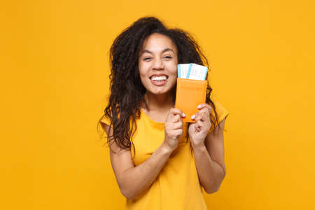 Joyful young african american woman girl in casual t-shirt posing isolated on yellow orange background in studio. People lifestyle concept. Mock up copy space. Hold passport boarding pass tickets.