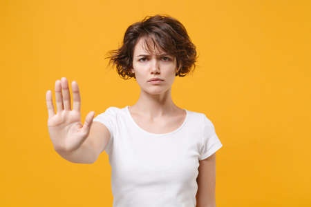 Displeased young brunette woman girl in white t-shirt posing isolated on yellow orange background studio portrait. People emotion lifestyle concept. Mock up copy space. Showing stop gesture with palm.