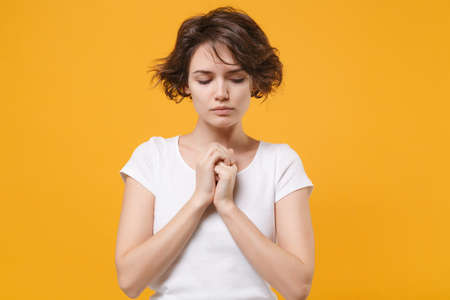 Young brunette woman in white t-shirt posing isolated on yellow orange wall background studio portrait. People lifestyle concept. Mock up copy space. Holding hands folded in prayer, looking down.