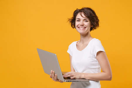 Pretty young brunette woman girl in white t-shirt posing isolated on yellow orange background studio portrait. People emotions lifestyle concept. Mock up copy space. Working on laptop pc computer. 免版税图像