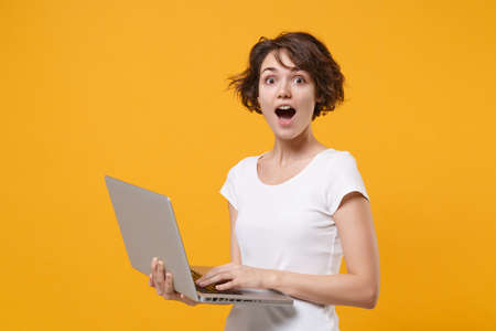Shocked young brunette woman girl in white t-shirt posing isolated on yellow orange background studio portrait. People emotions lifestyle concept. Mock up copy space. Working on laptop pc computer. 免版税图像