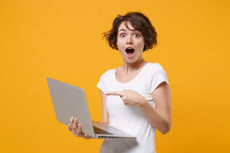 Shocked young brunette woman girl in white t-shirt posing isolated on yellow orange background in studio. People lifestyle concept. Mock up copy space. Pointing index finger on laptop pc computer. 免版税图像