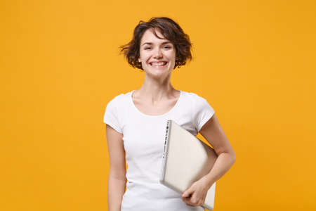 Smiling young brunette woman girl in white t-shirt posing isolated on yellow orange background studio portrait. People sincere emotions lifestyle concept. Mock up copy space. Hold laptop pc computer.