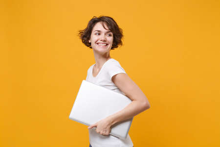 Smiling young brunette woman girl in white t-shirt posing isolated on yellow orange background studio portrait. People lifestyle concept. Mock up copy space. Hold laptop pc computer looking aside. 免版税图像