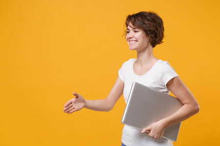 Smiling young brunette woman in white t-shirt posing isolated on yellow background. People lifestyle concept. Mock up copy space. Hold laptop pc computer standing with outstretched hand for greeting.