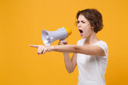Angry young brunette woman in white t-shirt posing isolated on yellow orange background studio portrait. People lifestyle concept. Mock up copy space. Scream in megaphone, pointing index finger aside. Stockfoto - 152814211