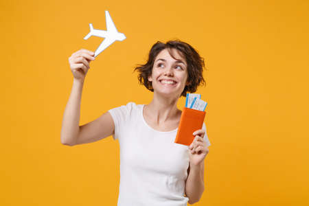 Cheerful young brunette woman girl in white t-shirt posing isolated on yellow orange wall background. People lifestyle concept. Mock up copy space. Hold passport boarding pass ticket paper airplane.